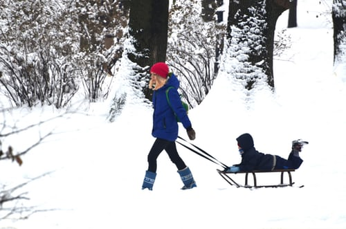 Mom with Child on Snow Sled